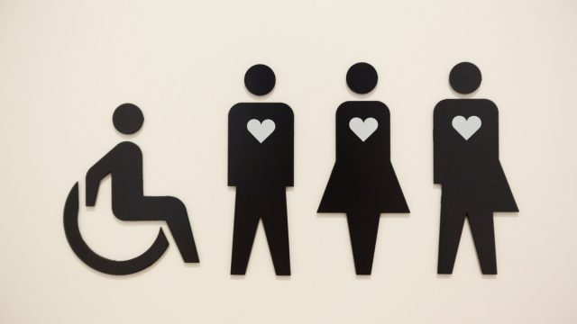 a sign on a toilet door showing four people in a line, one in a wheelchair and the other three with heart symbols on their chests.