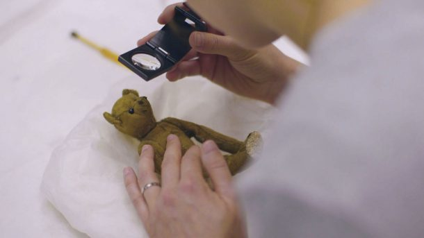 Small teddy bear, Little Tommy Tittlemouse, being inspected by conservator Nora Meller, with a magnifying glass