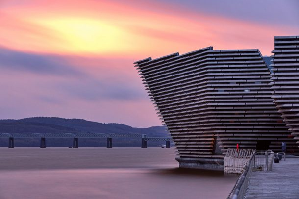 V&A Dundee leaning over the Tay on a purple sunset evening.