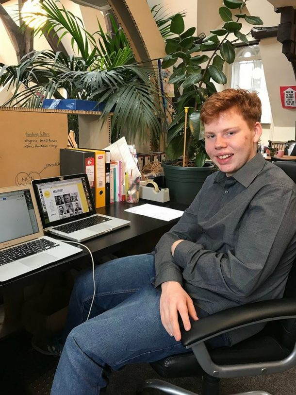 Photo of Andrew sitting in a desk chair in front of two laptops surrounded by houseplants.