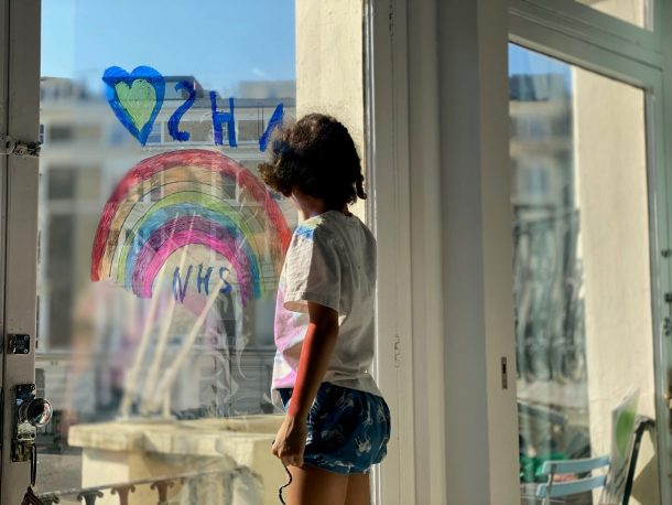 A child looks out a window, decorated with a rainbow