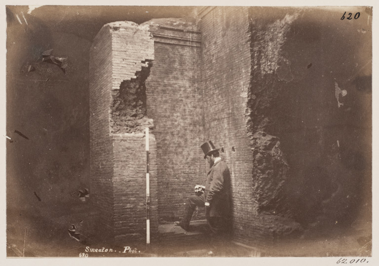 Photograph of a man holding a skull in the Catacomb of S. Domitilla, Rome