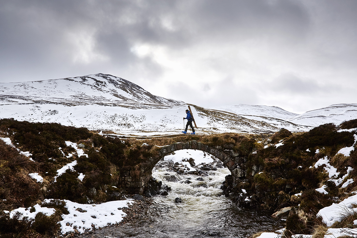 Jamie Kunta of Lonely Mountain Skis photographed by Alun Callend. Jamie walks across a stone bridge with skis over his shoulder in the Scottish Highlands.