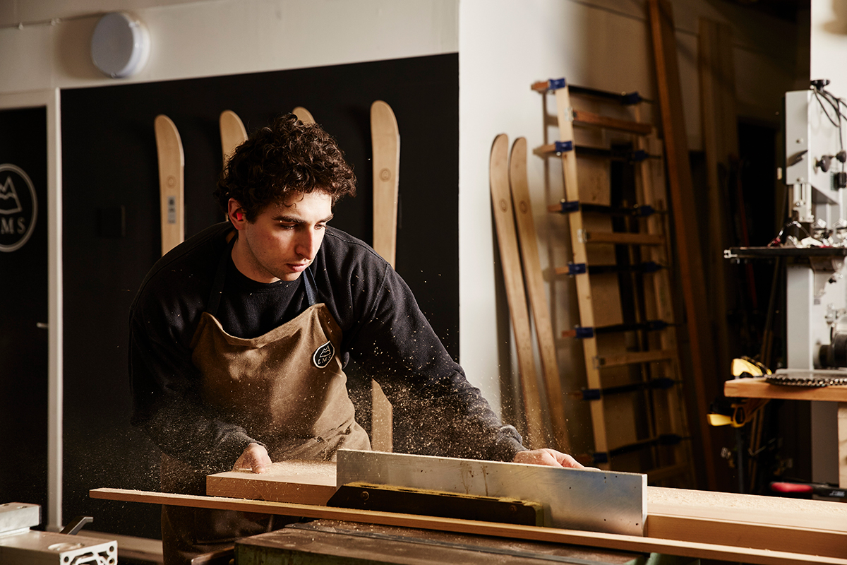 Alun Callender wearing a brown apron working wood in his workshop.