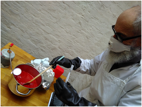 Senior V&A furniture conservator Dr Nigel Harman adding the lead minium to the linseed oil
