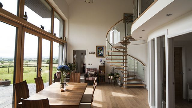 Interior view of the Passivhaus Hayshed showing a spiral staircase leading up to a mezzanine and one side of the room entirely windows.
