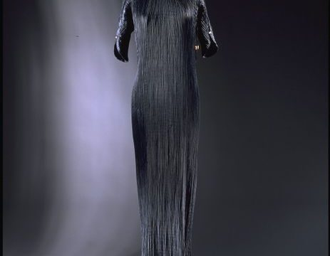 Black pleated silk Delphos dress mounted on a mannequin.
