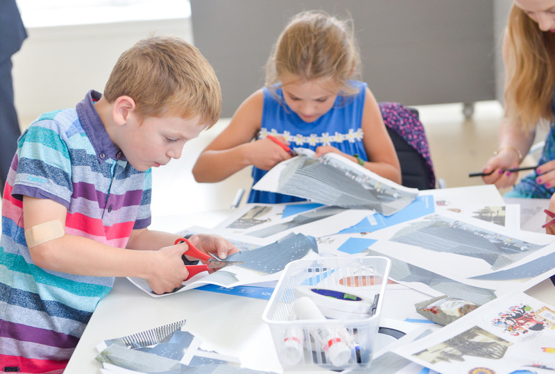 children with paper and scissors crafting at a table.