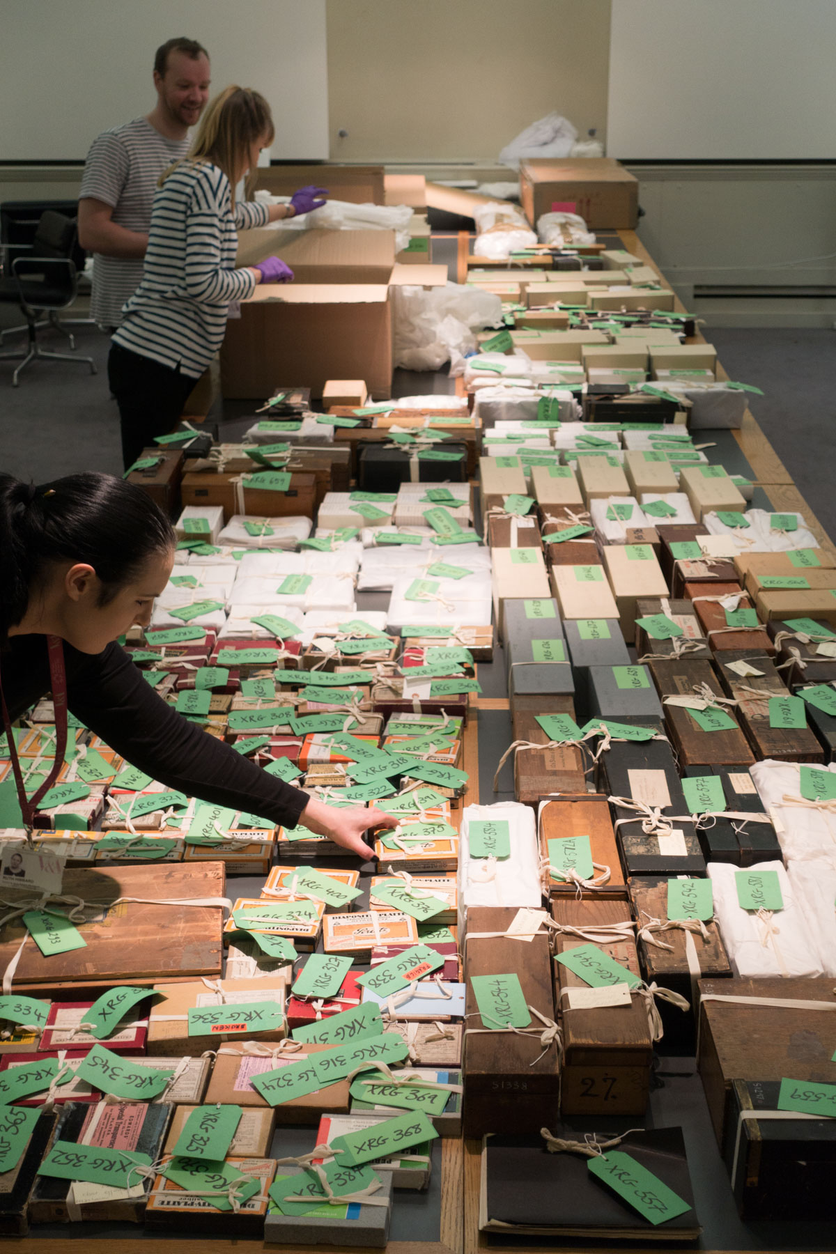 Image of V&A staff looking at a talbe of labelled boxes of glass plate negatives