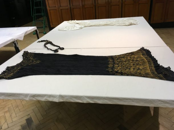 Two Delphos dresses out for a Clothworkers' appointment. One is black with gold fleur-de-lis, the other is white.