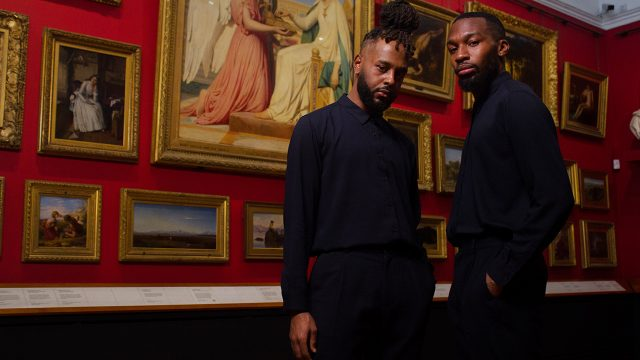 Two dancers stood in a red gallery