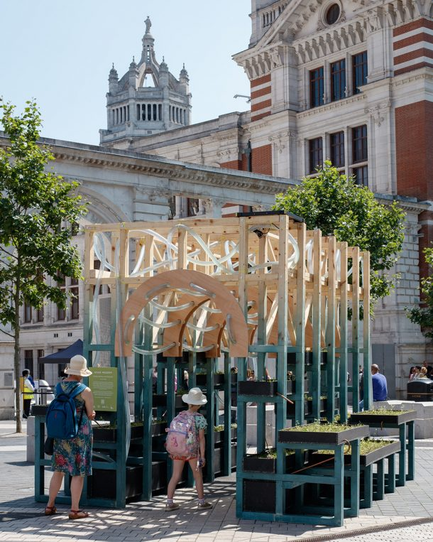 Algae Meadow installation. Wooden archway surrounded by square wooden structure, with tubes connecting parts. Accompanied by small table-like structures holding trays of greenery.