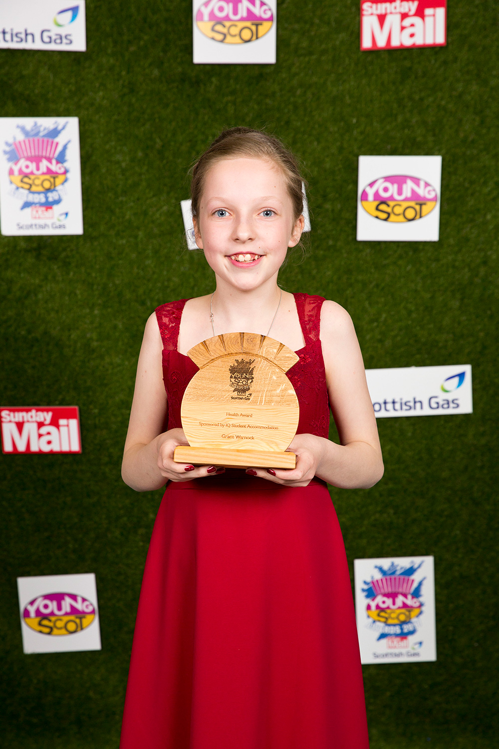 Grace, a young girl, wearing a red dress and holding up her Young Scot award