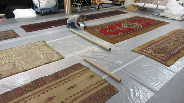 The author examining carpets in store at Blythe House