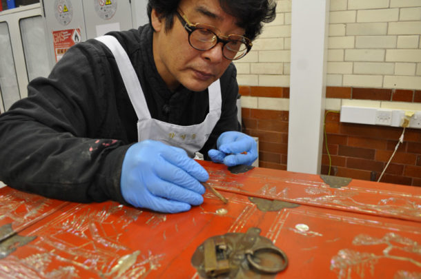 Mr Yang applying clay and rice starch paste to fill crack in lacquer surface