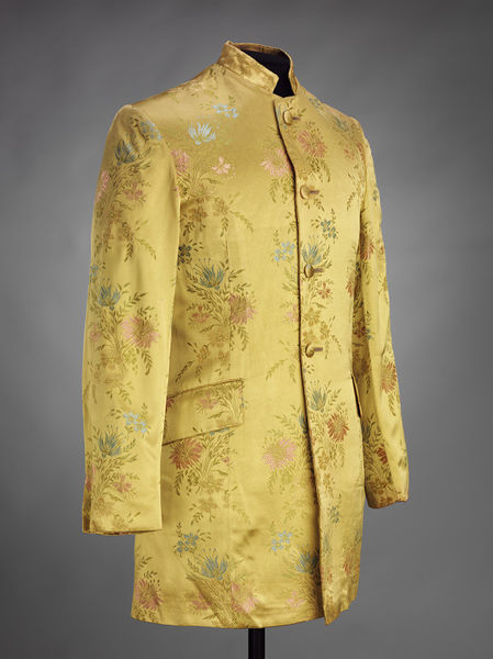 Nehru style jacket, characterised by the stand collar and long line cut. This jacket is made from a synthetic woven brocade fabric, with a yellow ground and floral motif in blue, pink and green. The jacket buttons from neck to waist with four self-covered buttons.
