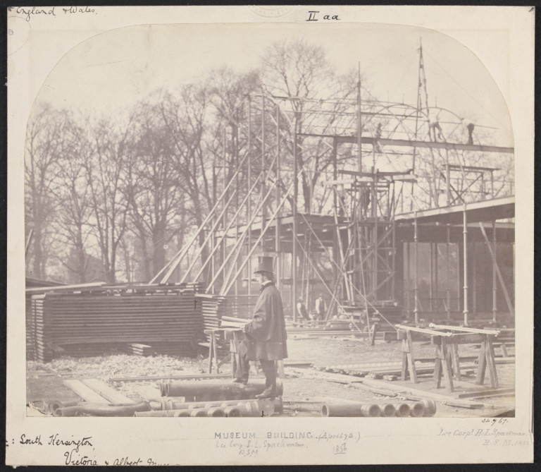 Exterior view of the South Kensington Museum (the 'Brompton Boilers') under construction with Sergeant Benjamin L. Spackman in the foreground