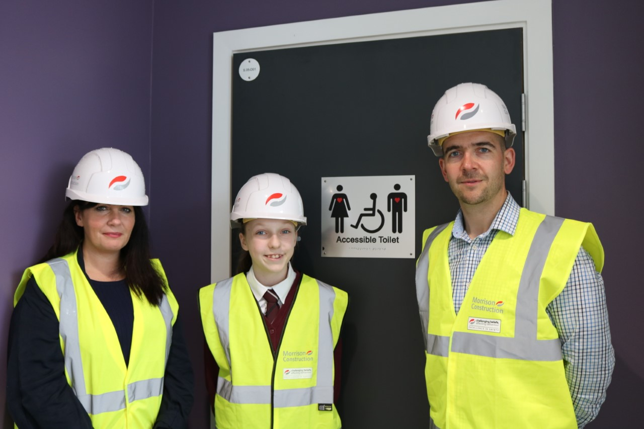 Three people in hi vis jackets stood in front of a bathroom door with grace's sign on it, welcoming all people to use the bathroom, including those with invisible disabilities.