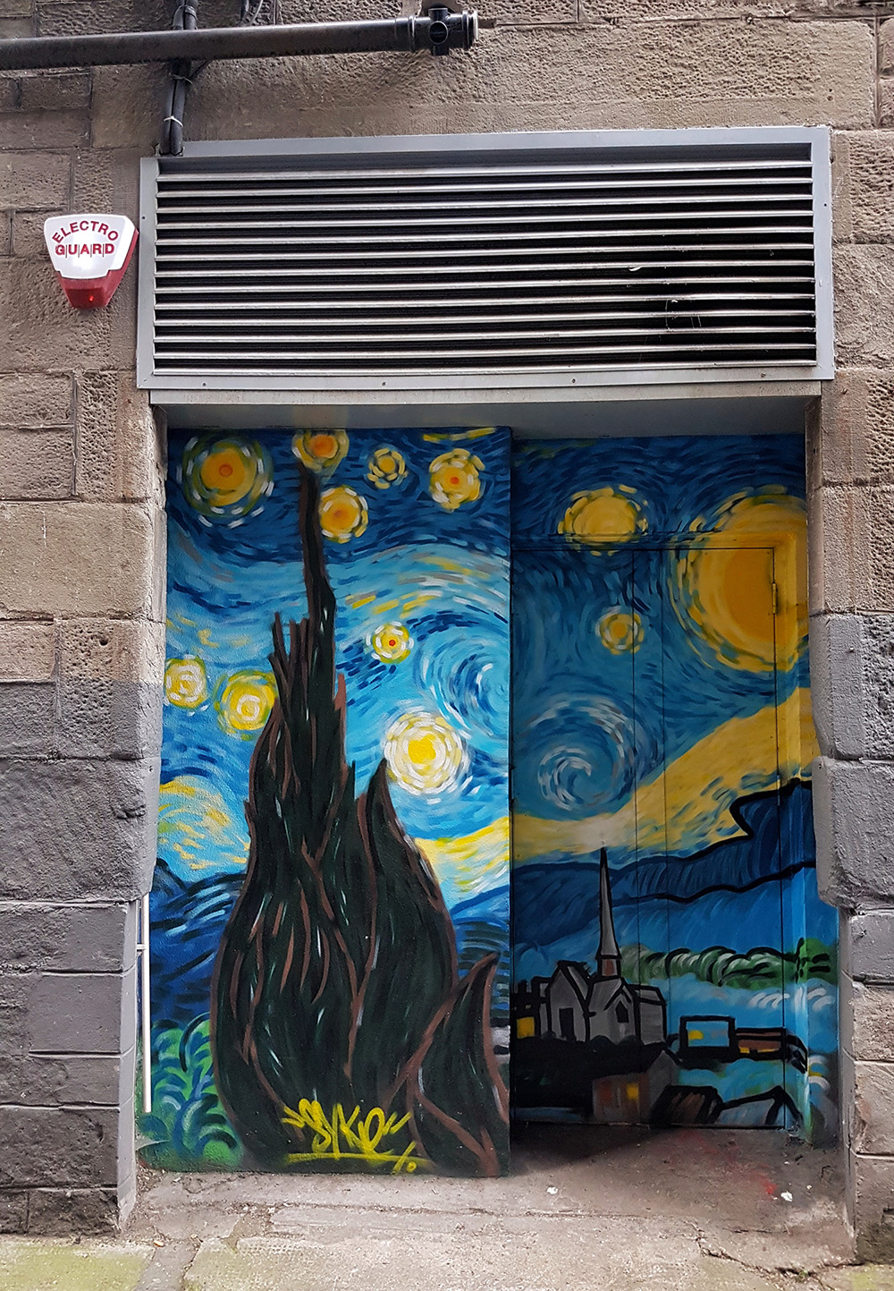 A painted doorway in an alley way. The doorway is painted with a tribute to van Gogh's Starry Night.