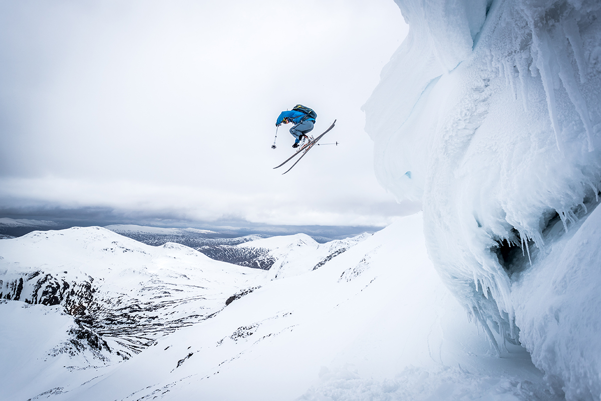 person skiing off the side of a large snowy side of a hill