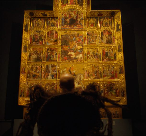 Elemental character looking up at the glowing golden altarpiece