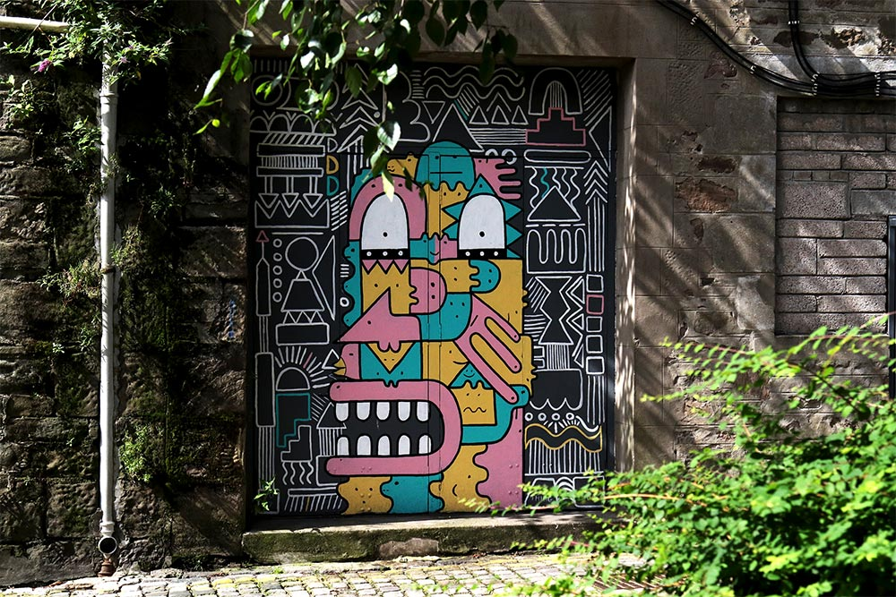 A painted door in an alleyway. The door iis yellow, pink and green and is a graphic and surreal looking face.