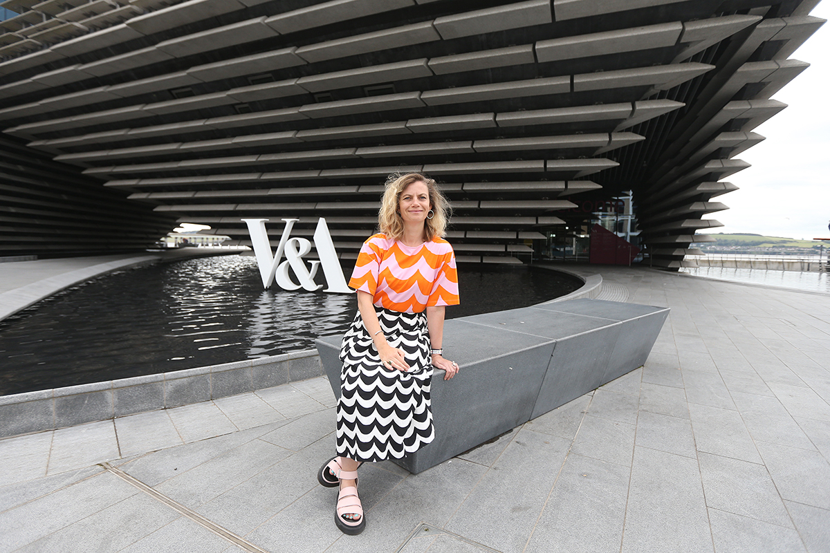 Woman leaning on a bench outside of V&A Dundee