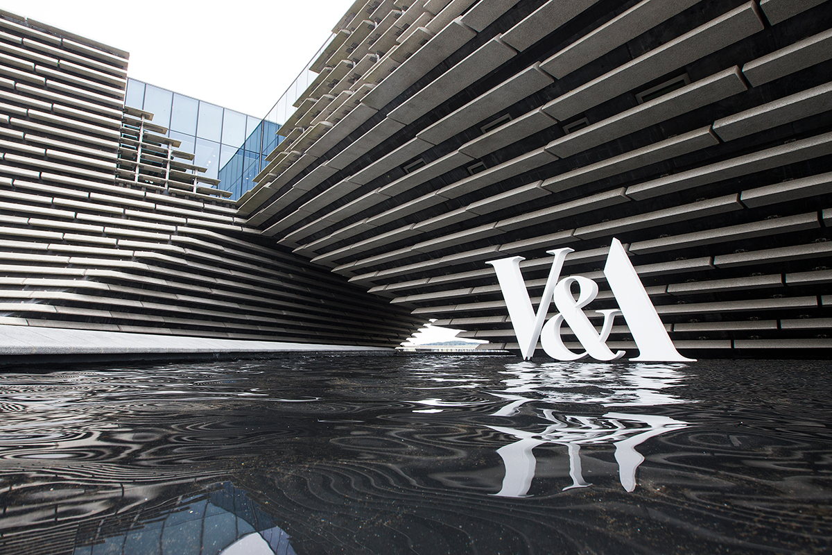 White V&A sign in front of V&A Dundee's grey stone clad facade.