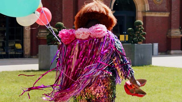 Person in a sharply cut orange wig, wearing a pink and purple sparkly cloak, holding balloons in one hand and sparkly red shoes in the other