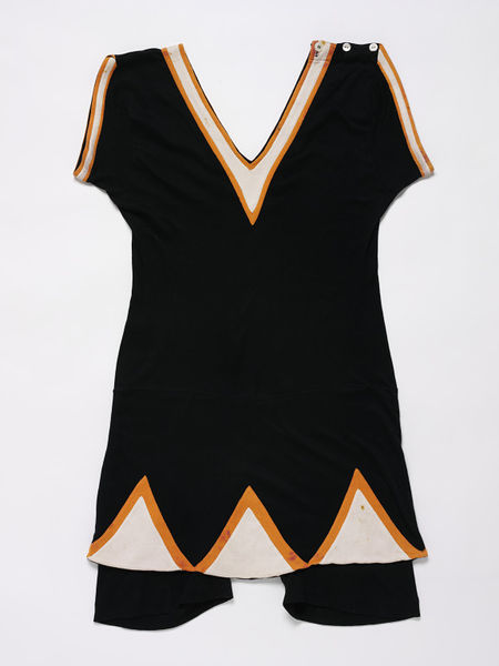 Woman's bathing costume of cotton jersey. In one piece with an attached modesty skirt. Black with orange and white Deco-style triangles around the edge of the skirt.
