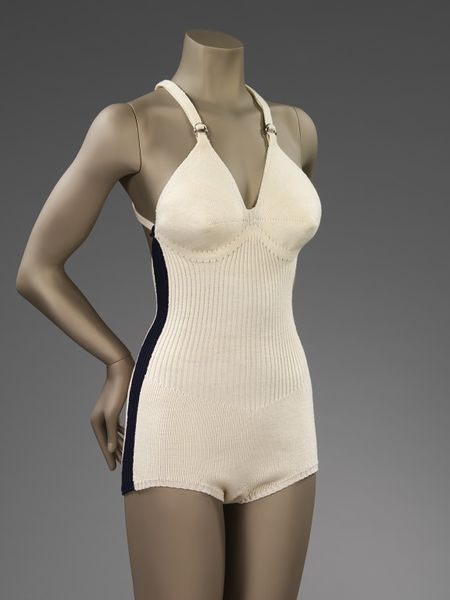 Bathing costume made of machine-knitted wool. Made in one-piece. White with a navy stripe down both sides. The straps cross over at the low cut back and through two chrome D loops at the front. Unlined. Made in stocking stitch with a ribbed waist panel. The bust is fashioned.
