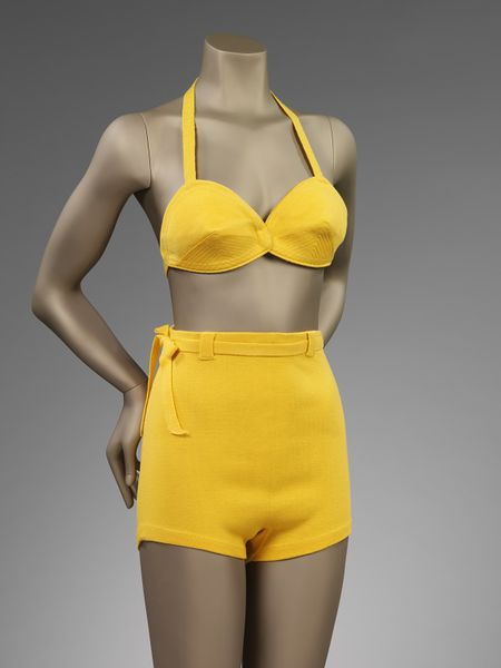 Two-piece bathing suit made of yellow wool jersey comprising of a pair of shorts and brassiere top. Brassiere top with a crossed strap fastening.
