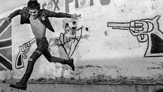 A man jumps in front of graffiti