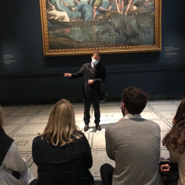 A tour guide presenting in the Raphael Court at the V&A