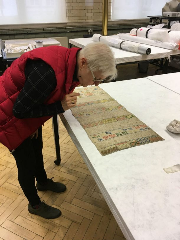 Inez Giles at the Clothworkers' Centre, inspecting an object