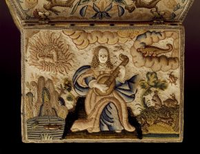 Part of an embroidered casket. The flat lid is embroidered outside with the figure of Music dressed as a fashionable lady playing a lute, with representations of the four elements - air, fire, earth and water - in the four corners. There are areas of raised work and applied pearls. The edge of the lid is embroidered with a small geometric pattern in laid floss silks.