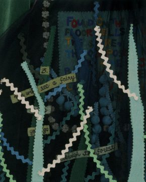 Close up of part of this ensemble. This layered net overdress uses appliqué to create a forest. The wood is suggested by applied strips of felt with pinked edges topstitched in white cotton and overlapping lengths of green, blue and white rick-rack braid. Additional braid and yellow ribbon inscribed with instructions are visible through the net haze.