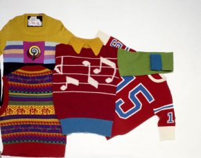 Long-sleeved jumper in machine-knitted wool, and stocking-stitch with a ribbed collar, cuffs and hem. With a design of musical notes in flat areas of colour and with Pop Art imagery. Shown with other jumpers.