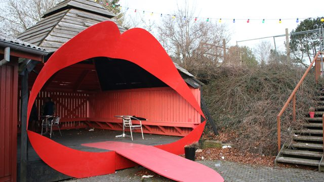 Big structure you can sit in shaped like a big mouth with red lips.