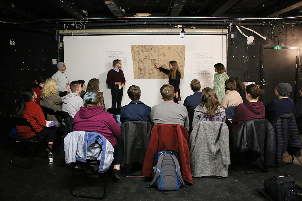 A group of young people sat in a room facing a white board with someone presenting a poster to them.