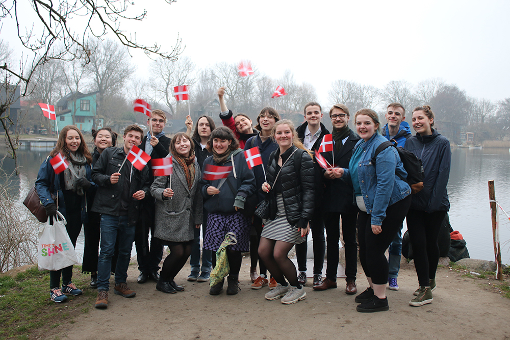 A group of young people stading in a row looking happy and animated, all carrying Danish flags.