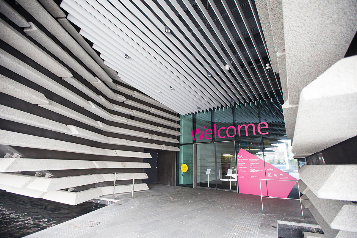 V&A Dundee entrance with a large pink welcome sign.